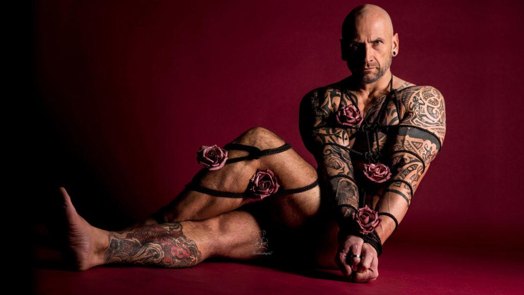 Seile, Fesseln und ein Männerkörper mit Blumen zum Valentinstag